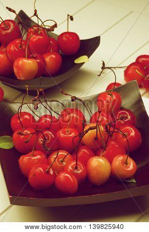 Fresh Ripe Sweet Maraschino Cherries on Black Wooden Plates closeup on Plank White background. Retro Styled