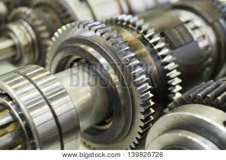close-up metal cog wheels in gearing at gear box
