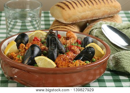 Paella with prawns and mussels in a teracotta dish