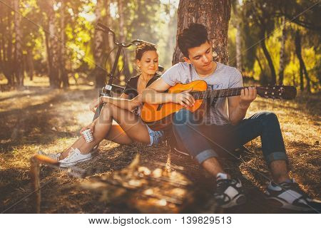 Teen boy sitting with his girlfriend by a tree, having a picnic and playing guitar on a sunny autumn day in forest. Teenagers loving couple relaxing by bonfire outdoors