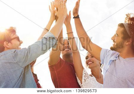 Group of happy friends high five and having fun together. Mixed race guys and girls celebrating success. Cheerful young men and women giving high five to each other.