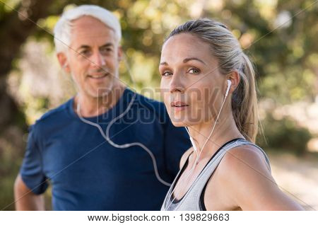 Senior couple resting after a long run in the park. Tired mature woman listening to music while relaxing after jogging. Senior woman looking at camera after training outdoor.
