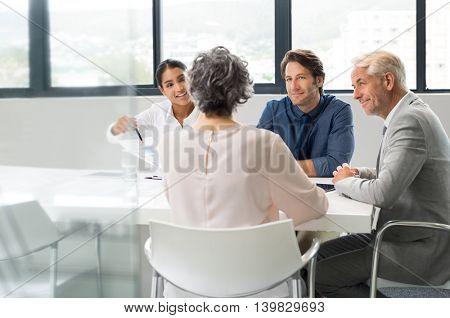 Multiethnic business people holding a meeting to sum up the results of the year. Group of happy team during a meeting in a board room. Young businesswoman showing a business graph of the company.