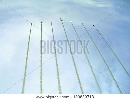 Group of airplanes with long contrails in the air