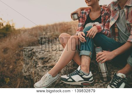 Cropped shot of young man and woman sitting on a stone with thermos. Teenagers loving couple wearing casual clothes relaxing outdoors