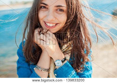 Beautiful sunny portrait of a shy girl looking at the camera with lake background. Teenage girl holding hands at face because of modesty