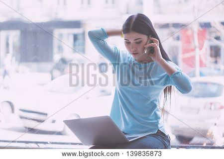 Busy lady. Confident and serious young woman sitting on a window sill and using laptop while being in a cafe and talking on a smart phone