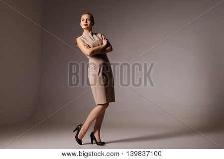 Portrait of happy businesswoman with arms crossed standing over brown background. Vertical shot.