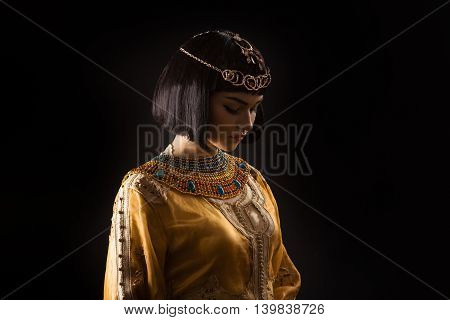 Fashion Stylish Beauty Portrait with Black Short Haircut and Professional Make-Up of Cleopatra Over Black. Beautiful Girl's Face Close-up.