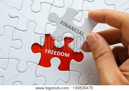 Hand Holding Piece Of Jigsaw Puzzle With Word Financial Freedom.