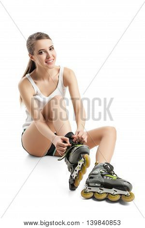 Pretty happy girl with rollerskates sitting on floor