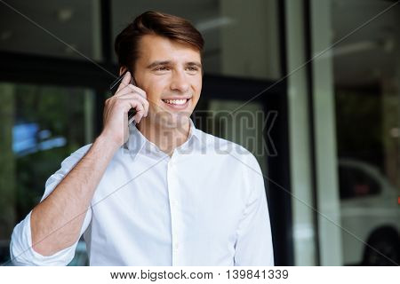 Closeup of happy young businessman talking on mobile phone near buiness center