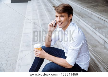 Smiling young businessman drinking coffee and talking on cell phone outdors