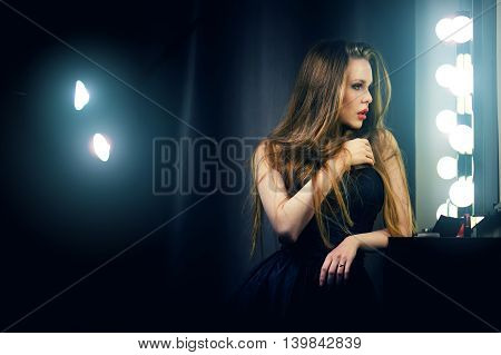 Beautiful sexy young caucasian woman in black dress looking into makeup mirror at herself. Backstage dramatic shot.