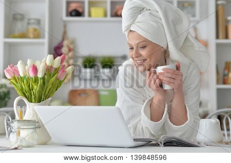 beautiful young woman wearing a white bathrobe with laptop and drinking tea at home