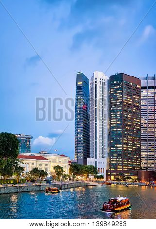 Ferry And Skyscrapers Of Financial Center In Singapore At Dusk