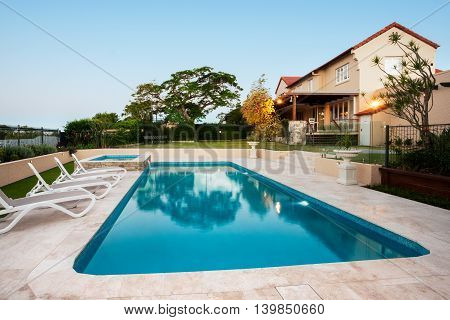 Light blue water swimming pool of a luxurious mansion with chairs around it. there are flashing lights on the modern house