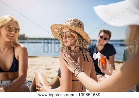 Girl Applying Suntan Cream On Her Friend