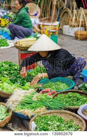 Asian Trader Selling Fresh Greens In The Street Market