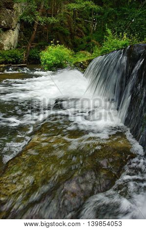 Weir on the wild river in a forest in Czech Switzerland