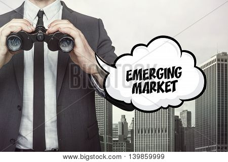 Emerging market text on speech bubble with businessman holding binoculars on city background