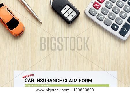 Top view of approved car insurance claim form with car key car toy and calculator on wooden desk.