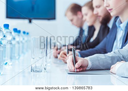 Close-up of a conference table with a glass and bottles of water and people taking notes in the blurry background