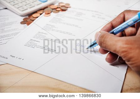 Use time and money for cure concept Hand with pen and bill and coins and calculator on wooden table vintage style