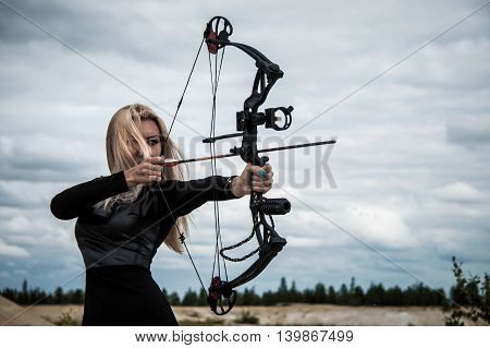 Young woman with a compound bow over clouds poster