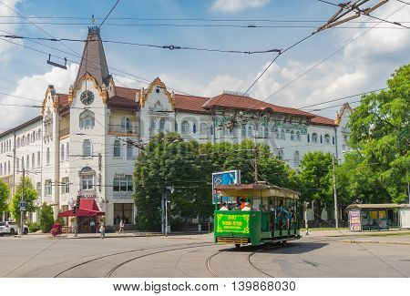DNEPROPETROVSK UKRAINE - JULY 10, 2016: Central part of the Dnepropetrovsk city with hotel Ukraine and ancient tram turning on a crossing at weekend day in Dnepropetrovsk, Ukraine at July 10, 2016