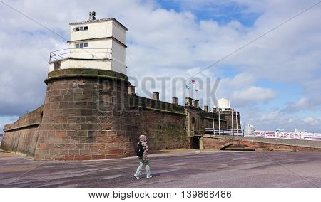 NEW BRIGHTON, ENGLAND, JUNE 29. Fort Perch Rock on June 29, 2016, in New Brighton, England. A woman walks near to Fort Perch Rock New Brighton Merseyside England