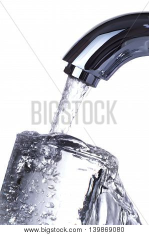 Water tap is pouring overflowing glass isolated on white background