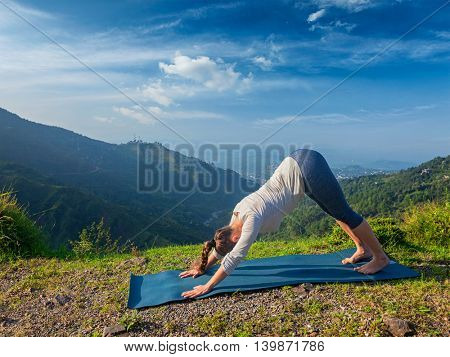 Yoga outdoors - young sporty fit woman doing Ashtanga Vinyasa Yoga asana Adho mukha svanasana - downward facing dog - in Surya Namaskar Sun Salutation outdoors in Himalayas in the morning