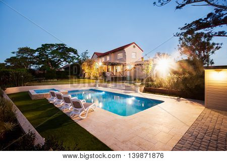 House And A Garden With A Pool Illuminate With Lights