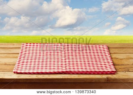 Empty wooden table with red checked tablecloth over beautiful landscape with green meadow and blue sky