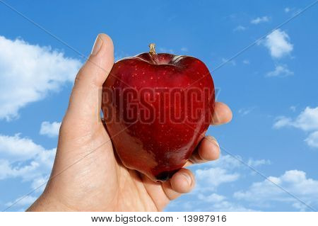 Apple In Hand Against Clouds