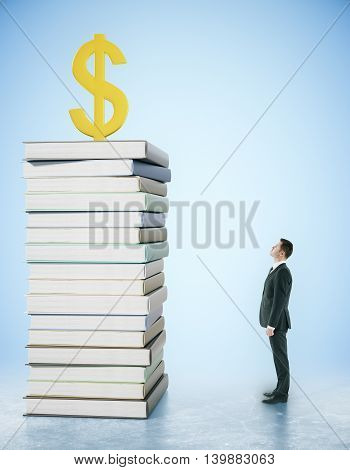 Businessman looking at dollar sign on top of book pile. Blue background. Financial growth and education concept. 3D Rendering