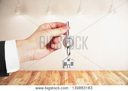 Businessman holding keys on light empty interior background. Real estate and mortgage concept