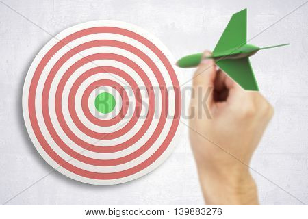 Targeting concept with businessman hand playing darts on light concrete wall background. 3D Rendering