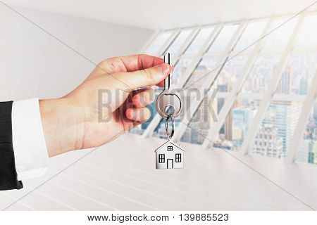 Businessman holding keys on white interior background. Real estate and mortgage concept