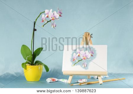 Collage with orchid flower, easel and watercolors. Digital picture on an easel stylized watercolor.