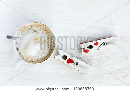 frothy cappuccino placed on a table on which is a pair of lovers clothespins / craving love and coffee