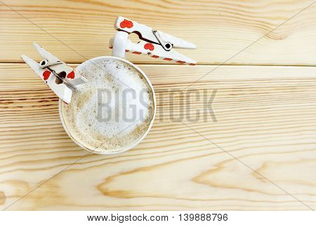 couple craving clothespins gripping the coffee mug with frothy milk foam top view / thirst for in love with coffee