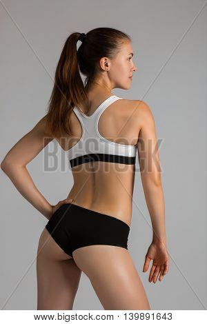 Beautiful super fit young woman showing off her perfect muscular body. Fitness model training with dumbbell weight . Perfect Slim Body with sturdy back muscles. Studio shot