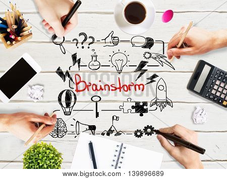 Brainstorm concept with businesspeople hands drawing sketch on light wooden office desktop with blank smartphone coffee cup stationery and other items