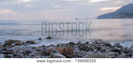 Misty water by the rocky shore creating dramatic effect