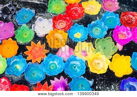 Floating flower candles by various colors on the pond