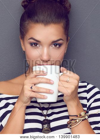 Portrait of young woman with cup tea or coffee.