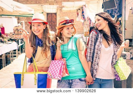 Cheerful girlfriends walking at flea market pointing out new fashion clothing - Carefree young women smiling and holding shopping bags outdoors -