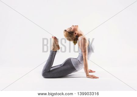 Sporty attractive young beautiful yoga posing on a studio background